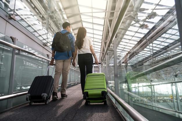 Viaggiatore asiatico delle coppie con le valigie all'aeroporto. viaggio e trasporto dell'amante con tecnologia