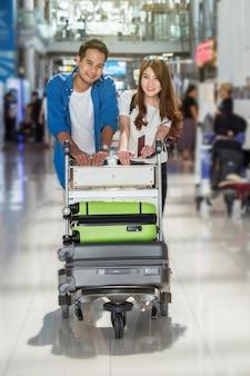 Viaggiatore asiatico delle coppie con le valigie all'aeroporto
