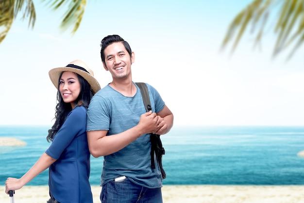 Coppia asiatica con cappello e zaino in viaggio verso la spiaggia con sfondo azzurro del cielo