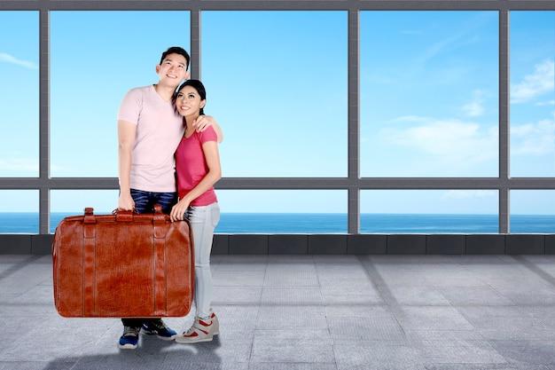 Coppia asiatica con una valigia nel resort con vista sull'oceano