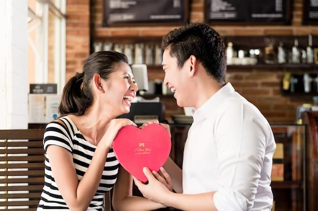 Coppia asiatica, donna e uomo, avendo data nella caffetteria con cuore rosso, festeggia l'anniversario