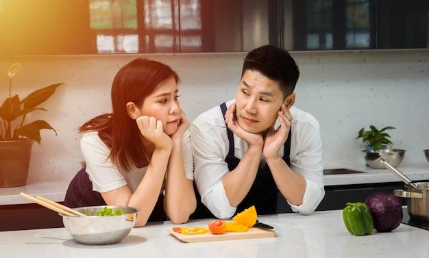 Cuoco unico asiatico delle coppie che cucina nella cucina.