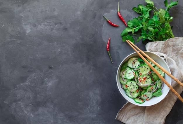 Insalata asiatica di cetrioli con cipolla rossa, peperoncino e sesamo nero in una ciotola bianca su cemento grigio.