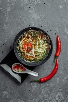 Cucina asiatica, zuppa di manzo fo in un piatto nero su sfondo scuro. zuppa di fo con brodo di manzo piccante, filetto di manzo, tagliatelle udon, pasta di peperoncino, cavolo di pechino, peperoncino, coriandolo, salsa piccante