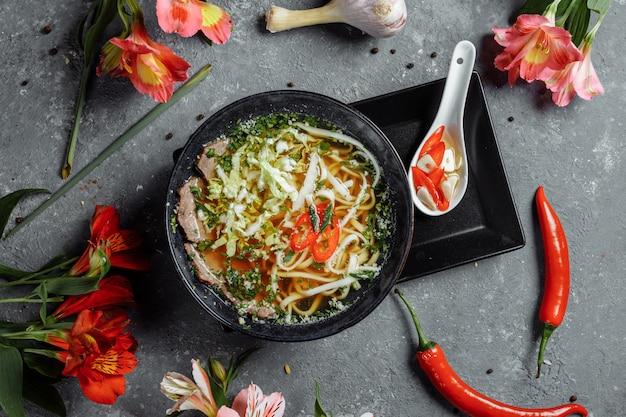 Cucina asiatica, zuppa di manzo in un piatto nero su uno sfondo scuro. zuppa fo con brodo di manzo piccante, filetto di manzo, noodles di udon, pasta di peperoncino