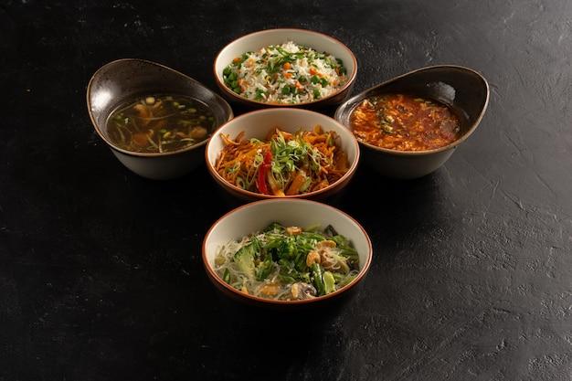 Cucina asiatica su un elegante tavolo da cucina in cemento nero, zuppe, riso, pasta all'uovo, pasta di vetro e contorni di verdure.