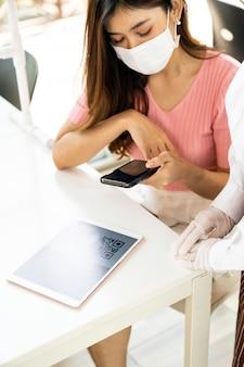 Menu online del codice qr di scansione del cliente asiatico dalla cameriera con maschera e visiera. il cliente si è seduto sul tavolo delle distanze sociali per un nuovo stile di vita normale al ristorante dopo la pandemia di coronavirus covid-19