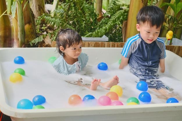Asiatico simpatico fratello maggiore e sorellina che si divertono a giocare con l'acqua, bolle di schiuma, giocattoli nel giardino sul retro, attività estive per bambini sani, calda giornata estiva, cose divertenti da fare a casa concetto