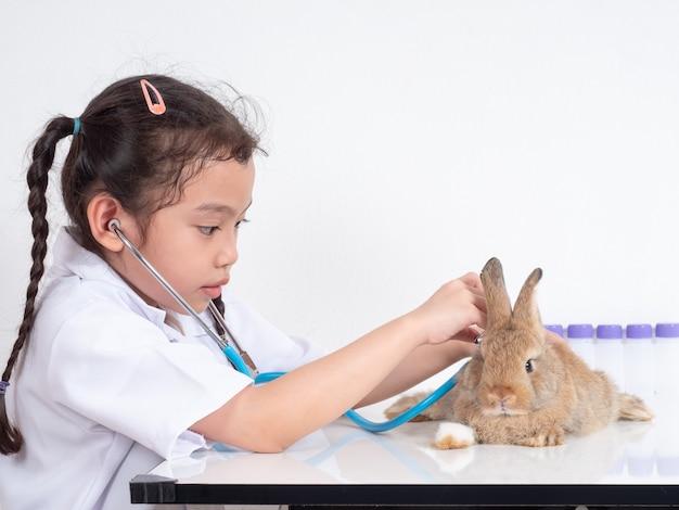 Ragazza carina asiatica di 6 anni che gioca al veterinario e usa lo stetoscopio che esamina un coniglio marrone del bambino sulla tavola bianca.