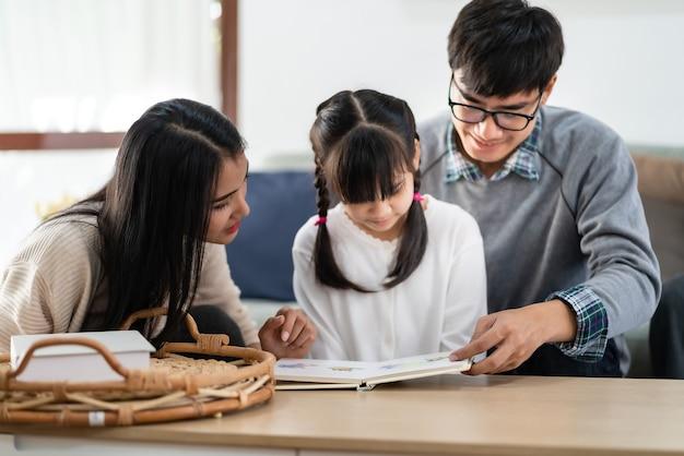 Ragazza sveglia asiatica che legge il libro del fumetto di storia con la sua mamma e papà in soggiorno