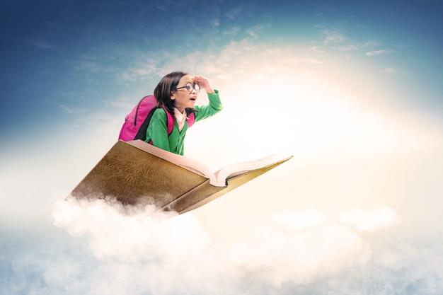 Ragazza sveglia asiatica con i vetri e lo zaino che si siedono sul libro con cielo blu