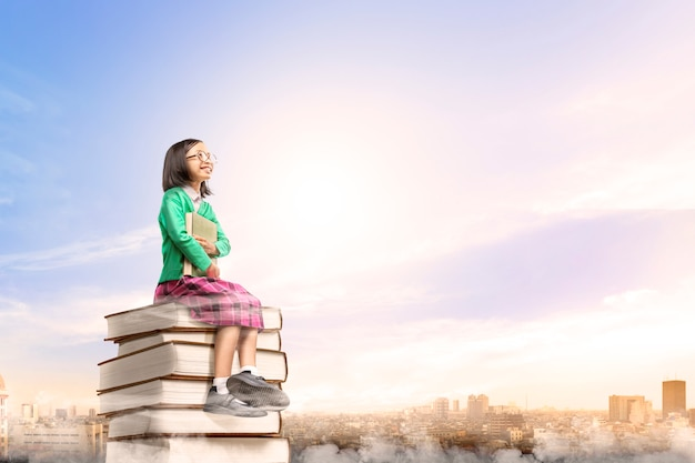 Ragazza sveglia asiatica con i vetri che tengono il libro mentre sedendosi sulla pila di libri con la città e il cielo blu