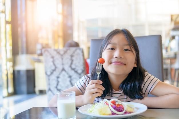 Bambina sveglia asiatica che mangia pomodoro fresco e insalata la mattina. sano e rilassarsi sul concetto di vacanza