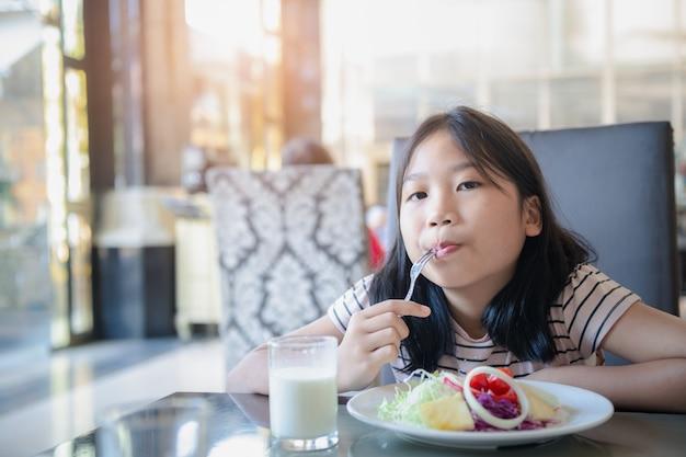 Bambina sveglia asiatica che mangia pomodoro fresco e insalata la mattina in hotel. sano e rilassarsi sul concetto di vacanza