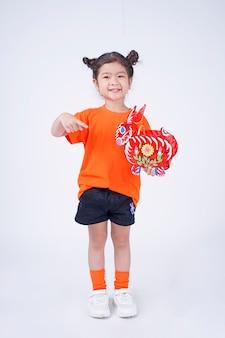 Ragazzino sveglio asiatico della bambina con l'espressione adorabile che tiene la lanterna di festival della luna