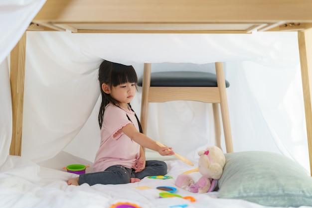 La bambina sveglia asiatica gioca cucinando e alimentando il cibo alla sua bambola