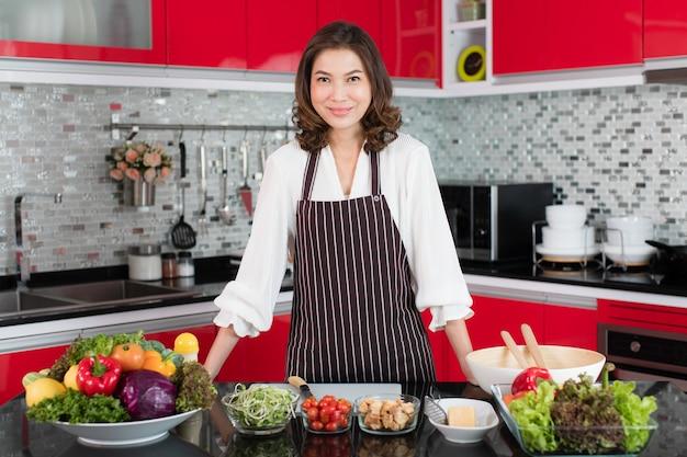 Asiatica carina donna di mezza età in un grembiule in piedi sulla moderna cucina nuova tonalità di rosso con varie verdure e ingredienti per la preparazione di insalate. concetto per casalinga e madre di stile di vita.
