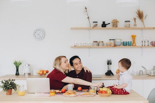 Papà asiatico e mamma europea lavorano con i loro gadget e il figlio fa colazione da solo. moderni problemi tecnologici.