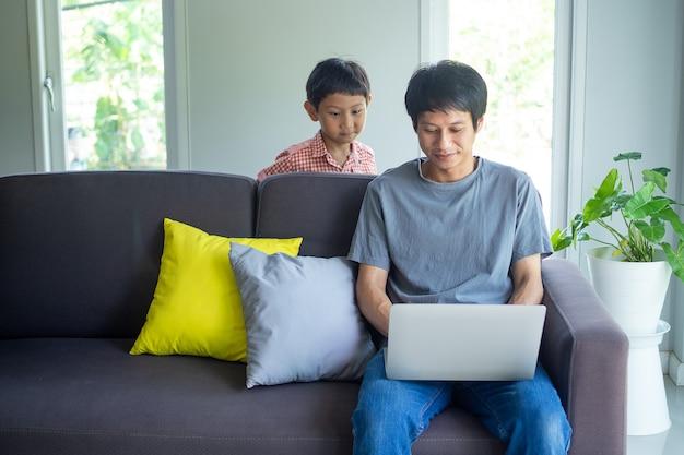 I papà asiatici lavorano da casa su un laptop. un figlio piccolo correva in giro e giocava con il giovane. relazione padre e figlio