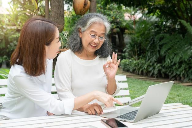 Figlia asiatica che insegna all'anziana donna anziana usa i social media in linea nel computer portatile dopo il pensionamento.