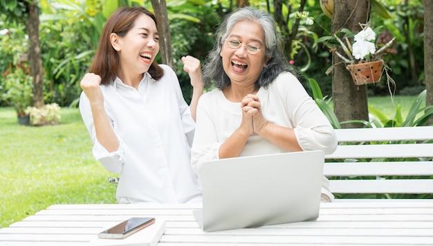 Figlia asiatica che insegna alla donna anziana anziana usa i media sociali in linea nel computer portatile dopo il pensionamento