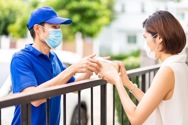 Asian consegna uomo in camicia blu che maneggia pacchetto e dà a giovane donna cliente a casa.