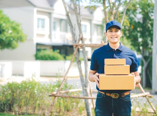 L'asiatico trasporta l'uomo nella scatola di pacchetto della tenuta uniforme blu