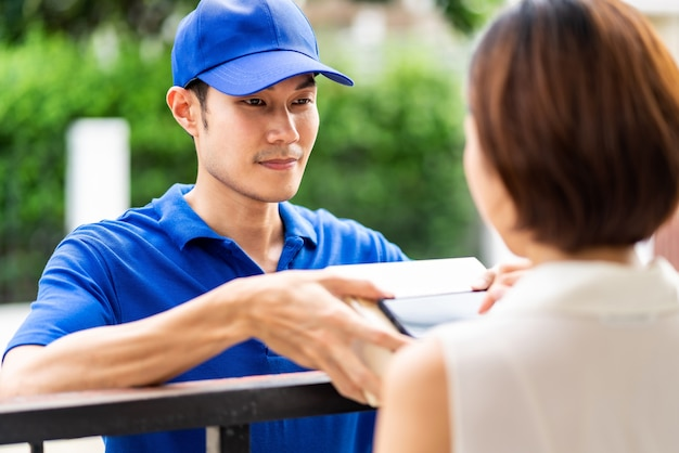 L'asiatico consegna l'uomo che maneggia la scatola del pacchetto alla donna asiatica davanti alla casa