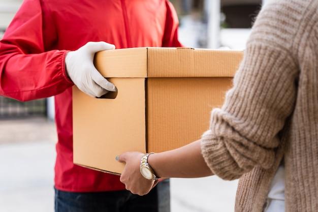 Un fattorino asiatico in uniforme rossa consegna un pacco a una cliente davanti alla casa. un postino e un servizio di consegna espresso consegnano pacchi durante la pandemia di covid19.