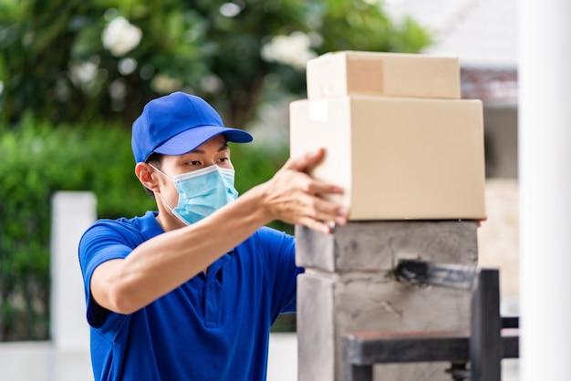 Uomo asiatico consegna con maschera facciale che gestisce la consegna senza contatto dei pacchetti