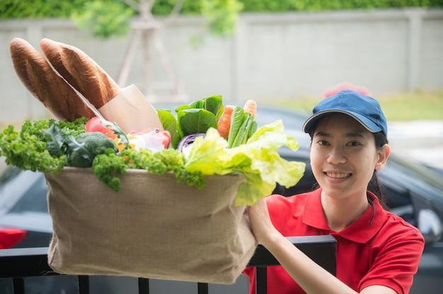 La donna asiatica consegna maneggia il sacchetto di cibo, da al cliente davanti alla casa