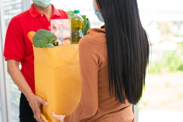 Uomo di consegna asiatico dal supermercato che indossa una maschera per il viso e che tiene un sacchetto di cibo fresco
