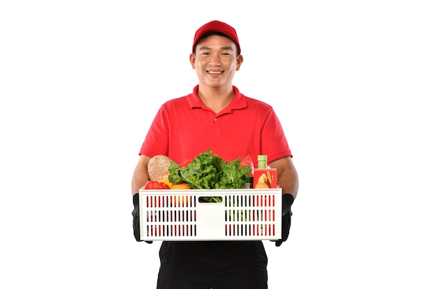 Il fattorino asiatico in uniforme rossa trasporta la scatola della drogheria nelle mani isolate su fondo bianco