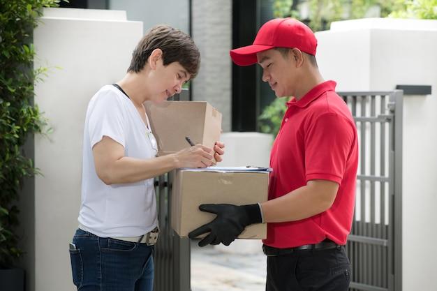 Uomo asiatico di consegna in uniforme rossa che consegna la cassetta dei pacchi al destinatario della donna a casa