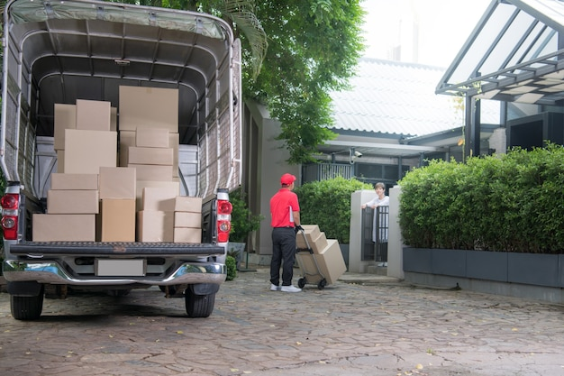 Uomo asiatico di consegna in uniforme rossa che consegna le cassette dei pacchi al destinatario della donna a casa