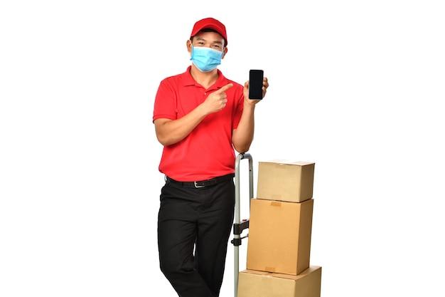 Uomo di consegna asiatico in uniforme rossa con scatola di cartone del pacco