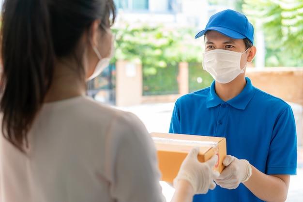 Fattorino asiatico che indossa maschera e guanto in uniforme blu che tiene scatole di cartone davanti casa e donna che accetta una consegna di scatole dal fattorino durante lo scoppio di covid-19.