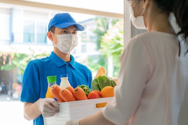 Il fattorino asiatico che indossa la maschera e il guanto con la scatola della spesa di cibo, frutta, verdura e bevanda danno al cliente della donna davanti alla casa durante il periodo dell'isolamento domestico.