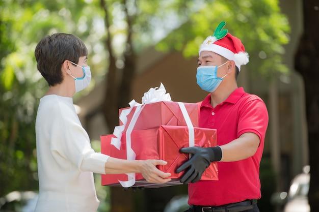 Uomo di consegna asiatico che indossa maschera e guanti in uniforme rossa e cappello di natale che consegna scatole regalo e presenti durante l'epidemia di covid-19 per il festival di natale