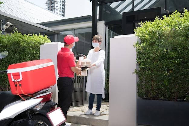 Uomo di consegna asiatico che indossa maschera e guanti in uniforme rossa che consegna il sacchetto di alimento e di bevanda al destinatario