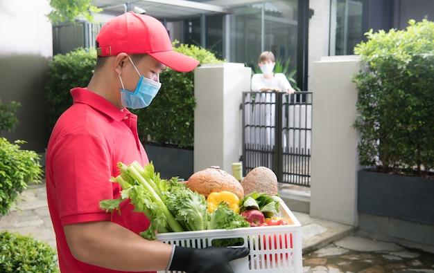 Uomo asiatico di consegna che indossa la maschera e guanti in uniforme rossa che trasporta la scatola di generi alimentari