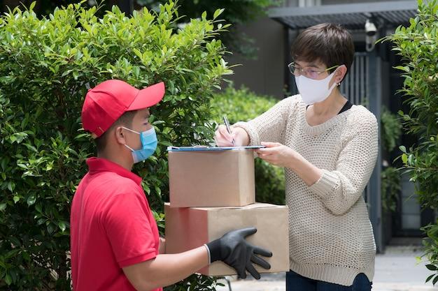 Uomo asiatico di consegna che indossa la maschera per il viso e guanti in uniforme rossa che consegna la cassetta dei pacchi al destinatario
