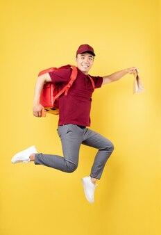 Uomo di consegna asiatico che indossa un'uniforme rossa che posa sulla parete gialla