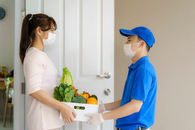 Uomo di consegna asiatico con scatola di generi alimentari di cibo
