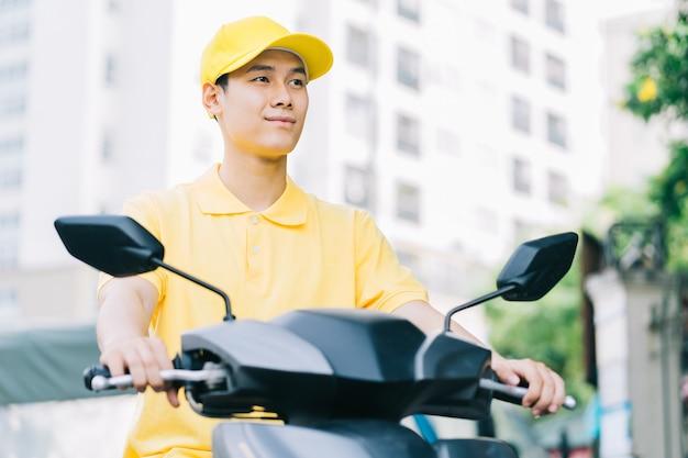 Il fattorino asiatico sta guidando la sua moto per consegnare al cliente