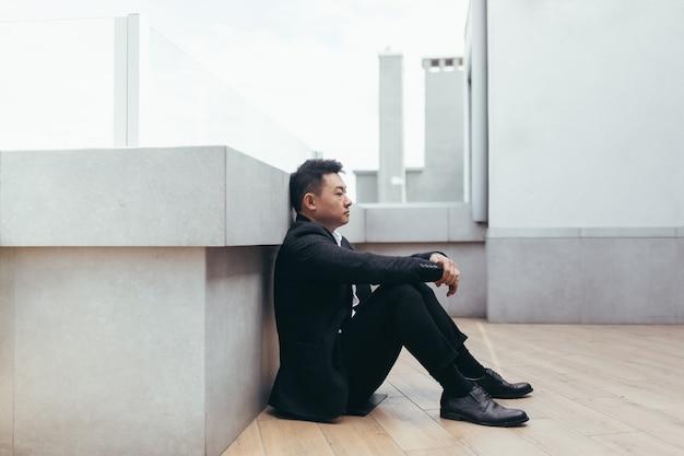 Uomo asiatico depresso seduto su una strada all'aperto vicino all'edificio del centro affari dell'ufficio