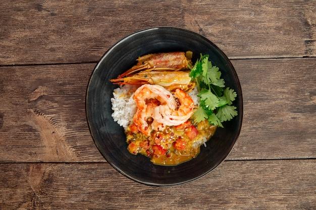 Piatto asiatico al curry con scampi e riso hikari