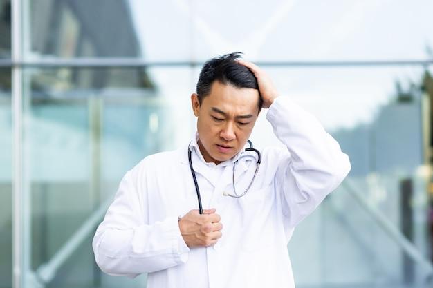Il medico asiatico è stanco dopo il lavoro, depresso e deluso dal lavoro svolto per strada vicino alla clinica
