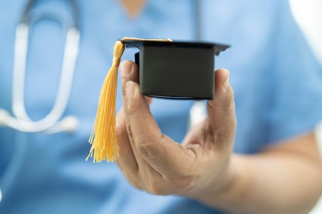 Lo studio medico asiatico impara con il cappello di laurea nel reparto ospedaliero in