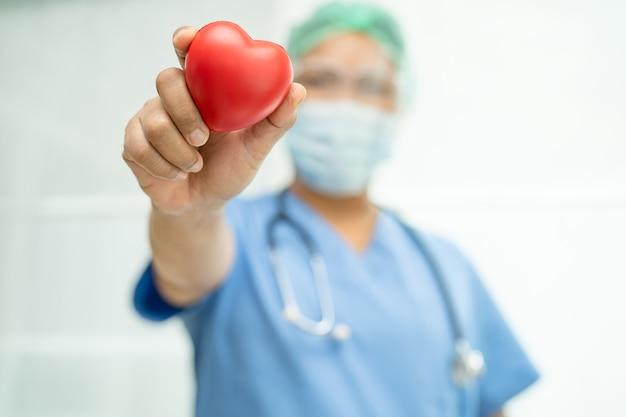 Medico asiatico che indossa visiera e tuta dpi nuova normalità per proteggere l'infezione di sicurezza covid-19 coronavirus che tiene in mano il cuore rosso in ospedale.
